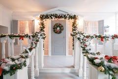 julskogen knurled morgon som snöig trails övervintrar wide klassiska lyxiga lägenheter med en vit spis, dekorerat träd, ljus soff Royaltyfri Bild