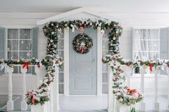julskogen knurled morgon som snöig trails övervintrar wide klassiska lyxiga lägenheter med en vit spis, dekorerat träd, ljus soff Arkivbild