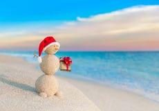 Julsnögubbe i jultomtenhatt med gåvan på solnedgångstranden Royaltyfria Bilder
