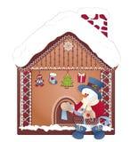 Julsnögubbe med gåvan och det ljust rödbrun huset royaltyfri fotografi