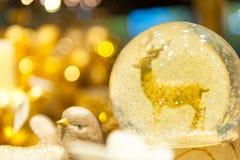 Julsnöjordklot med en hjort in inom Arkivfoton