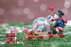 Julsnöjordklot med lyckliga snögubbear arkivbild
