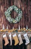 Julsockor på den dekorerade spisen, bakgrund av en trävägg med en grön krans Arkivbilder