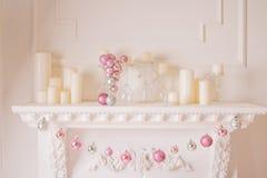 Julspis, hängande rosa prydnader, juldekorleksaker på brandstället, magisk berättelse för Xmas, i att tända inre royaltyfria foton