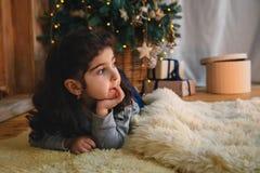 Julstående av den härliga lilla flickan som ligger på golv under julträdet Begrepp för Xmas för vinterferie och för nytt år royaltyfria foton