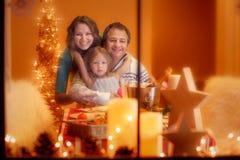 Julstående av den lyckliga familjen av hemmastadda tre Arkivbild