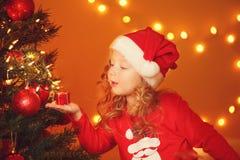 Julstående av den lyckliga flickan hemma Arkivbild
