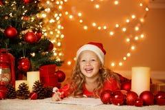 Julstående av den lyckliga flickan hemma Fotografering för Bildbyråer