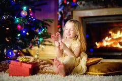 Julstående av den lyckliga lilla flickan vid en spis i en hemtrevlig mörk vardagsrum royaltyfria foton