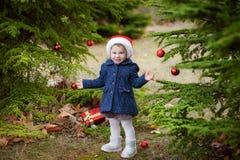 Julstående som ler barnlilla flickan i santa det röda near trädet royaltyfri foto