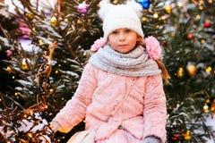 julståenden av den lyckliga barnflickan som går utomhus- snöig vinter, dekorerade träd på bakgrund arkivbilder