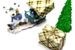 Julstatyett av en hjort med en släde, bärande gåvor för en hjort under julgranen som isoleras på en vit bakgrund royaltyfri foto