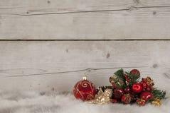 Julstilleben med den röda glass struntsaken och prydnader på fårskinn Royaltyfri Fotografi