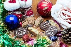 Julstilleben med ljust rödbrun honungkex, prydnader, sörjer, skor, gåvan, kranschokladgodis på en träbakgrund Fotografering för Bildbyråer