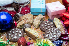 Julstilleben med ljust rödbrun honungkex, prydnader, sörjer, skor, gåvan, kranschokladgodis på en träbakgrund Arkivfoto