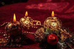 Julstilleben med sfäriska stearinljus på Bourgognebakgrund Royaltyfri Fotografi