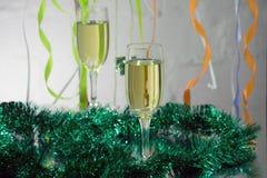 Julstilleben - två exponeringsglas av mousserande vin med guld- Xmas-garneringar på julgranbakgrund Arkivbilder