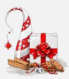 Julstilleben, vit gåvaask med det stora röda bandet, kakor, kanel- och klirrklockor och abstrakt chritmasträd Royaltyfri Foto