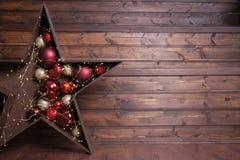 Julstjärna som göras av mörkt trä Girlanden glöder Röda lodisar royaltyfria foton