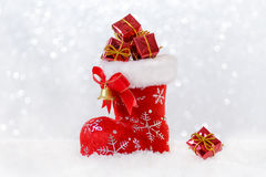 Julstrumpa med gåvor, kängan för santa ` s i snö, bokeh och snowflackes Arkivfoton