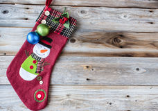 Julstrumpa med snögubben på den på en sida av gammal lantlig wood bakgrund med utrymme för text Royaltyfria Foton
