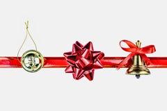Julsymboler och prydnader Julklocka, en röd pilbåge, en guld- julgranleksak Arkivfoto