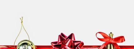 Julsymboler och prydnader Julklocka, en röd pilbåge, en guld- julgranleksak Arkivbild