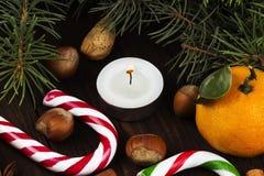 Julsymboler - strumpan, stearinljus, gran-trädet, tangerin, kan Arkivfoton