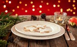 Jultabell - elegant vit platta med kakor, röd bakgrund Arkivbild