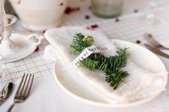 Jultabell: kniv och gaffel, servett och julgranfilial på en trätabell Dekor för ` s för nytt år av den festliga tabellen Arkivfoto