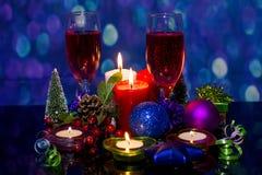 Jultabelldesign Exponeringsglas med alkoholdryckchampagne och beautifully dekorerade stearinljus arkivbild