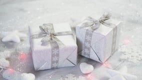Jultabellgarnering med två försilvrar gåvor och ljus med snöflingor och vita stjärnor arkivfilmer