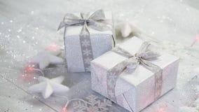 Jultabellgarnering med två försilvrar gåvor och ljus med snöflingor och vita stjärnor lager videofilmer
