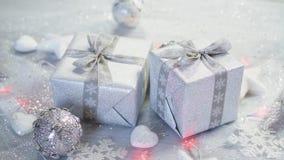 Jultabellgarnering med två försilvrar gåvor och ljus med snöflingor och vita stjärnor stock video