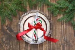 Jultabellinställning med godisrottingen och rött band som dekoren, tappningdishware, bestick och garneringar ombord Arkivbilder