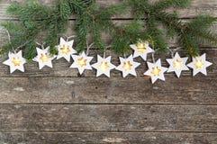 Jultema: hemtrevliga varma ljusgirlandstjärnor och granfilialer på lantlig träbakgrund Top beskådar över handen royaltyfria bilder