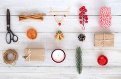 Jultemabakgrund med garneringar och gåvaaskar på det vita wood brädet royaltyfria foton