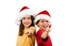 Jultid - flicka och pojke med Santa Claus Hat som visar det reko tecknet Royaltyfri Foto