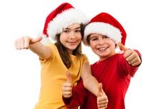 Jultid - flicka och pojke med Santa Claus Hat som visar det reko tecknet Arkivbilder