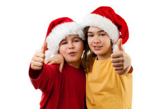 Jultid - flicka och pojke med Santa Claus Hat som visar det reko tecknet Arkivbild