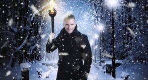 Jultid - man att gå under en snöig natt Arkivbilder