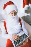 Jultomte med bärbar dator royaltyfri bild