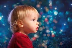 Jultomten behandla som ett barn att se fascinerad från sidan Fotografering för Bildbyråer