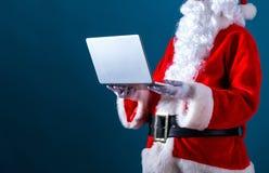 Jultomten genom att använda en bärbar dator royaltyfria foton