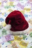 Jultomten hatt på hög av euroanmärkningar Arkivbilder