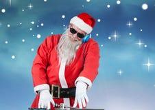 Jultomten i solglasögon som spelar dj Arkivbilder