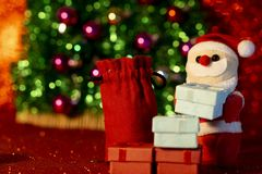 Jultomten med dekorativ bakgrund för julgåvaask arkivfoto