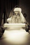 Jultomten med en lång jullista Arkivbilder