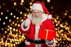 Jultomten med gåvan som ger upp tummen Royaltyfri Bild