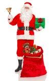 Jultomten med gåvor och en klocka Royaltyfri Foto